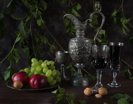 赤ワイン、クルミ、ブドウおよびネクタリンに暗い背景に緑の植物で覆われている満ちているアンティークのピッチャーと、ゴブレットの中世風の静物