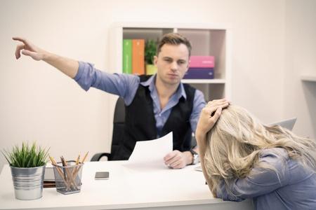 上司は若い不幸な女性従業員にドアを見せています。