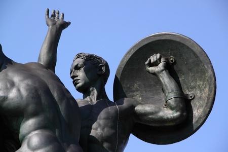 青空の背景上にシールド、若い兵士の銅像